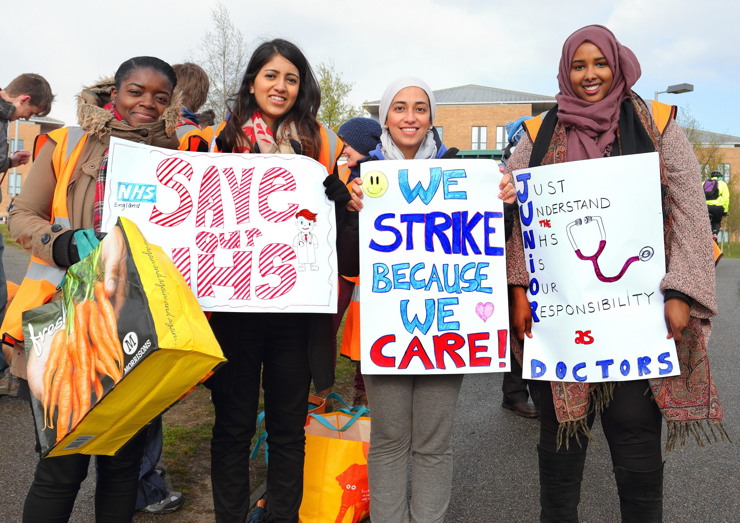 Four female junior doctors holding placards