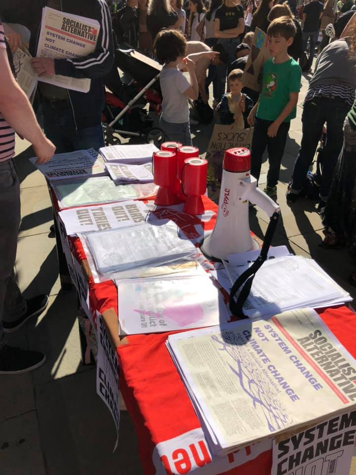 Table with signs saying 'system change not climate change' and 'Boris out, Tories out'